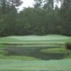 A view of a green protected by a pond at Abita Springs Golf & Country Club